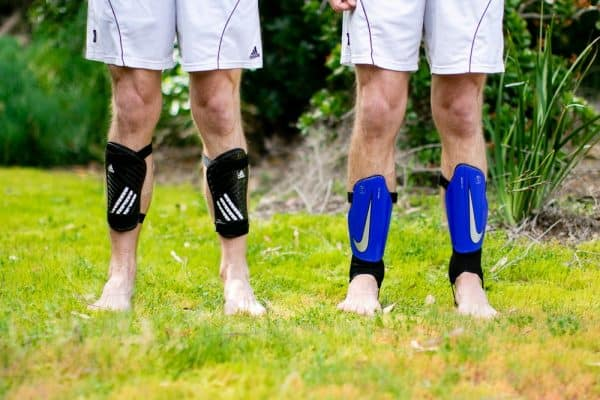 Two boys on a field wearing shin guards