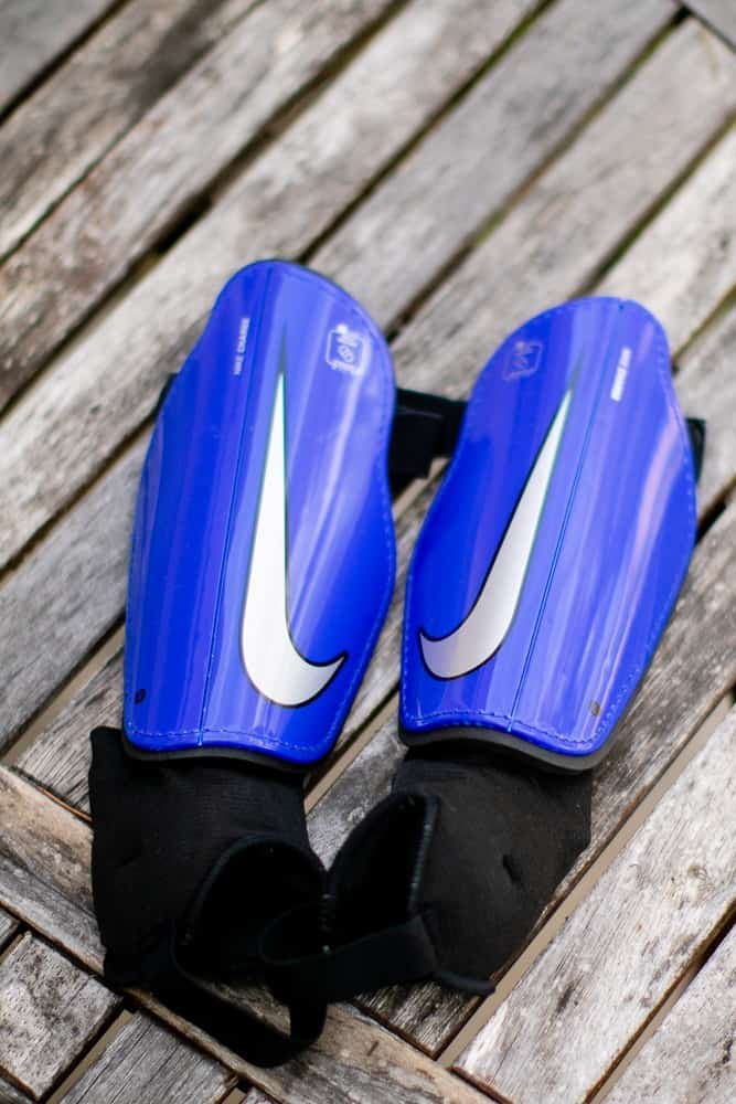 A pair of blue shin guards on wood
