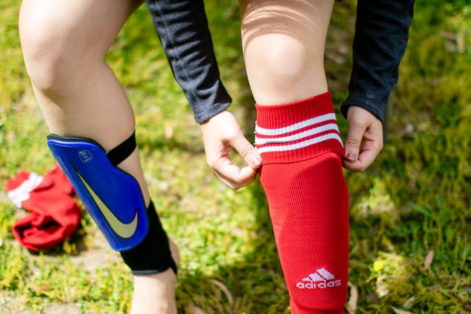 Woman trying on a red adidas soccer sock
