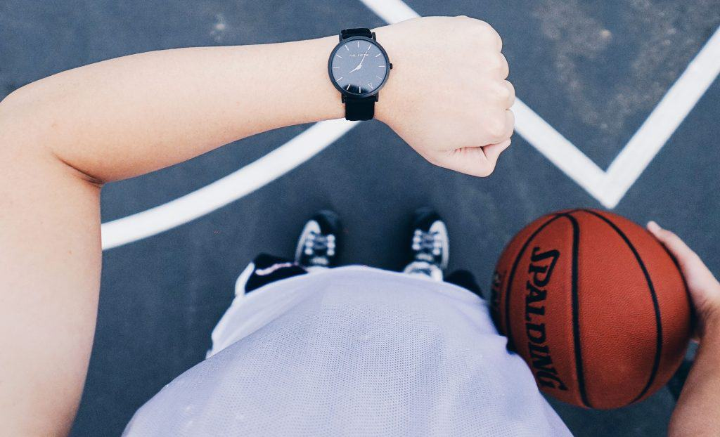 A man standing in a basketball court holding a ball and checking the time