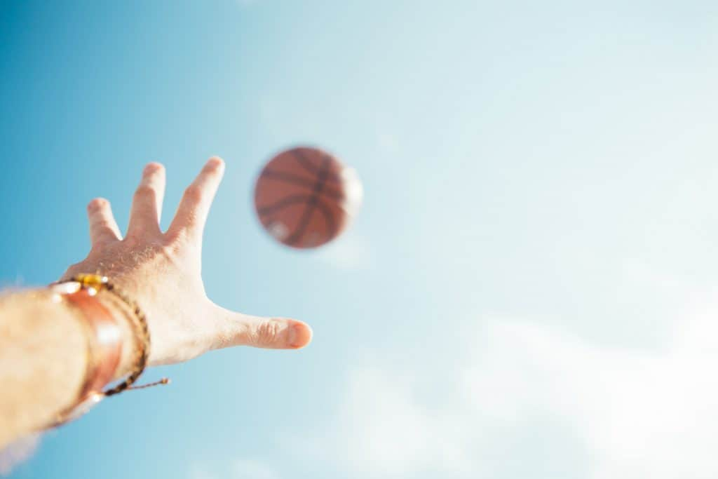 Hand letting go of a basketball in mid air