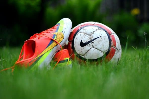 Soccer cleats next to a Nike soccer bal