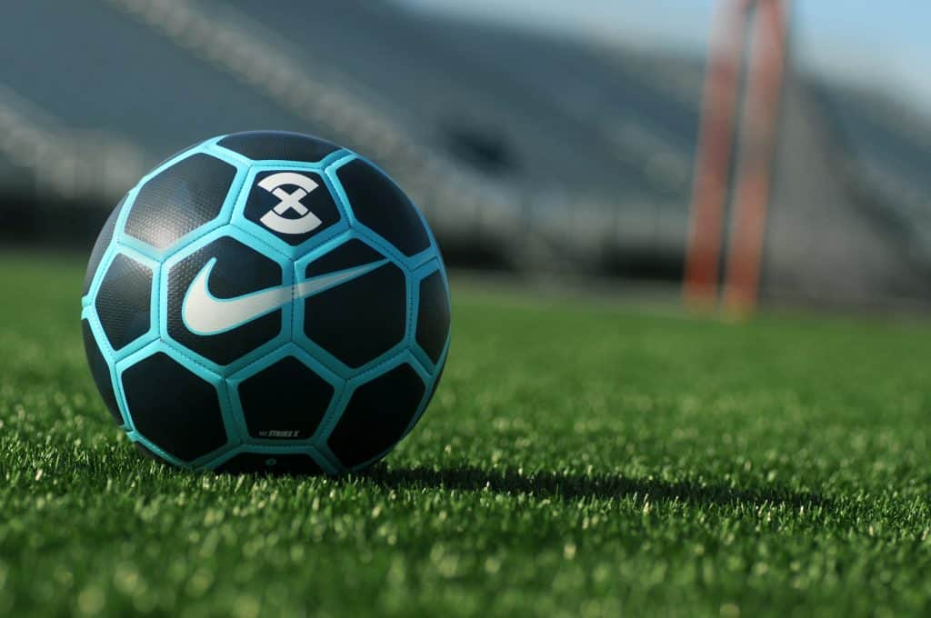 Close iup of a blue and black Nike soccer ball on a soccer field