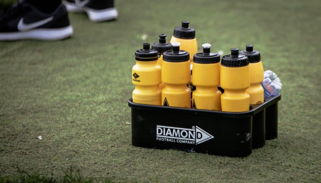 Yellow water bottles ina tray for soccer players