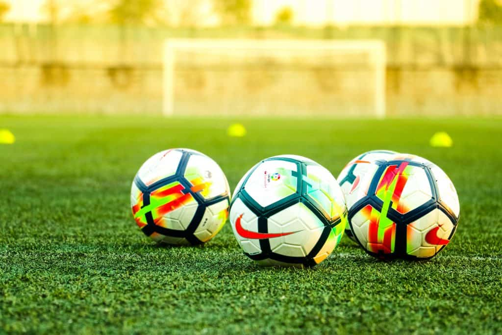 Four soccer balls sitting on a soccer field