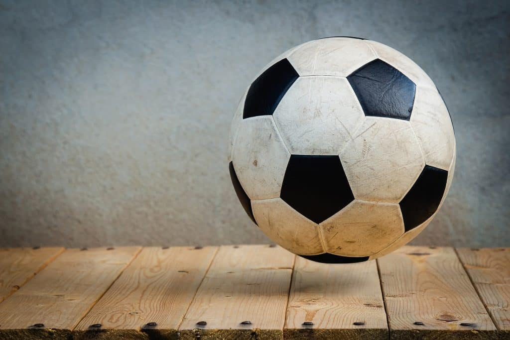 Black and white soccer ball on a wooden surface