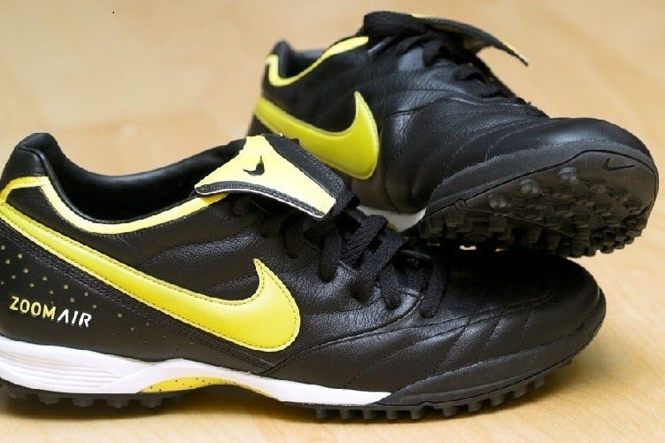 A pair of black and yellow soccer shoes