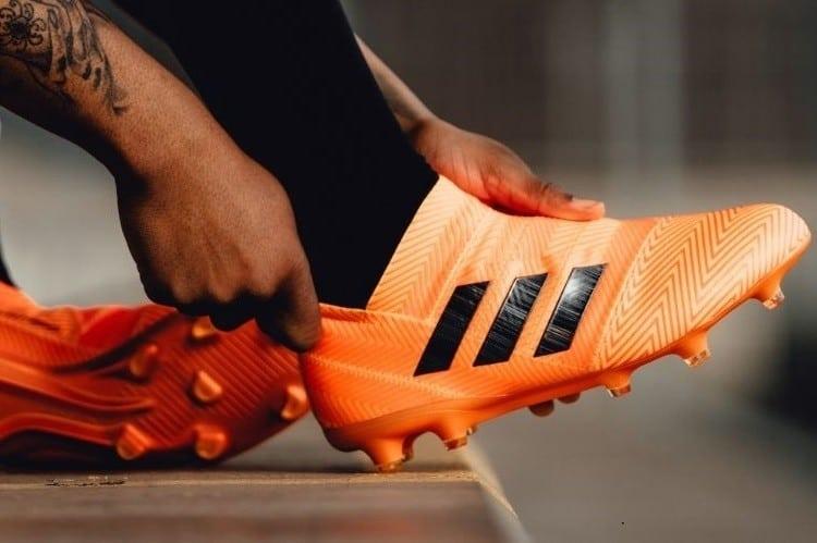 Man putting his pair of orange soccer shoes