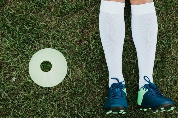 Man lies down wearing soccer cleats and socks