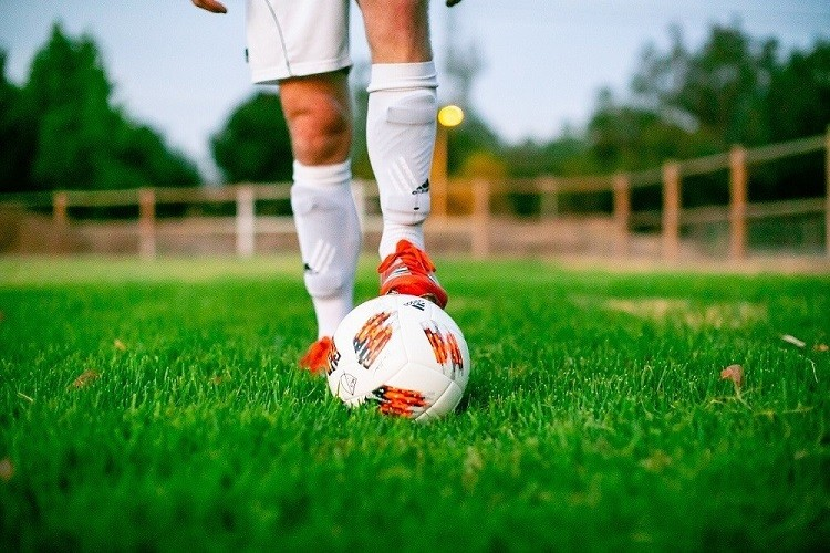 Person in a grass field with his foot on top of a soccer ball
