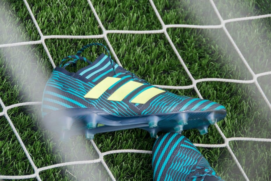 Pair of blue adidas soccer cleats on a goal net