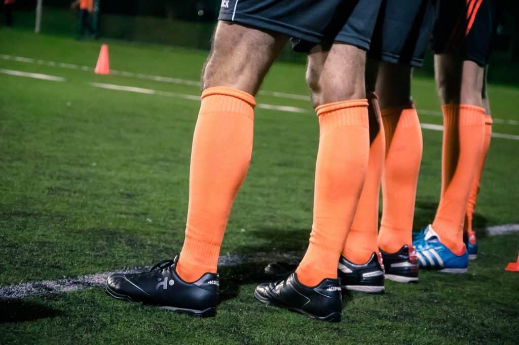 Men wearing orange soccer socks and cleats