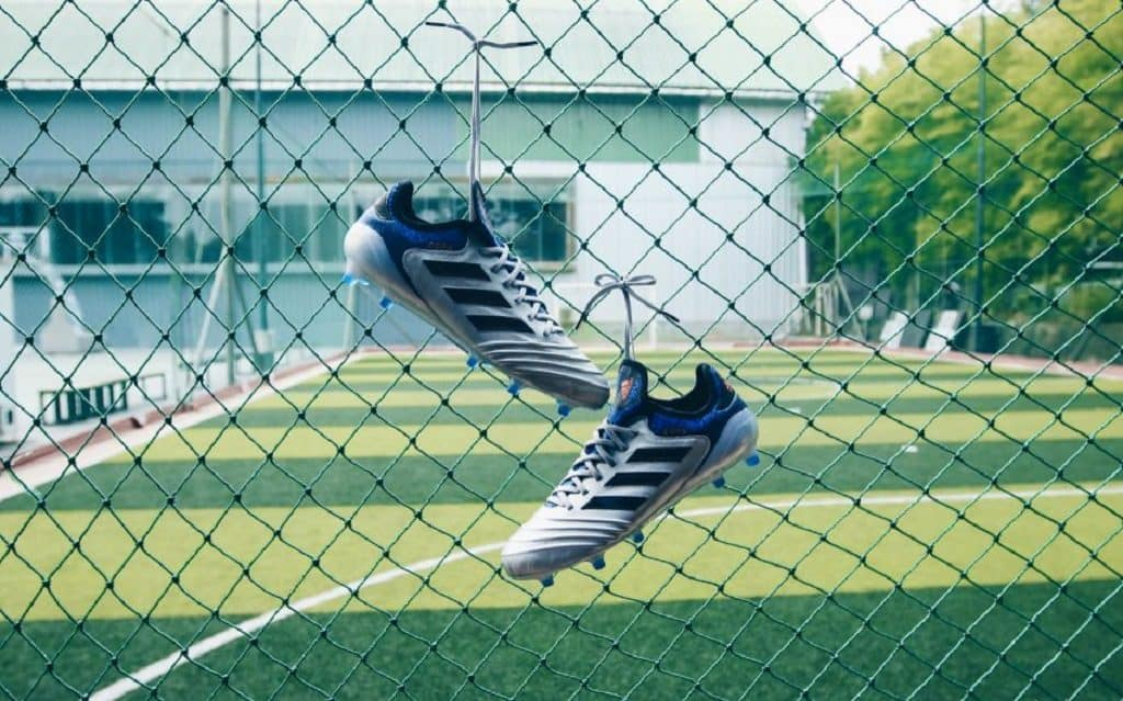 Two soccer cleats tied to a wire fence