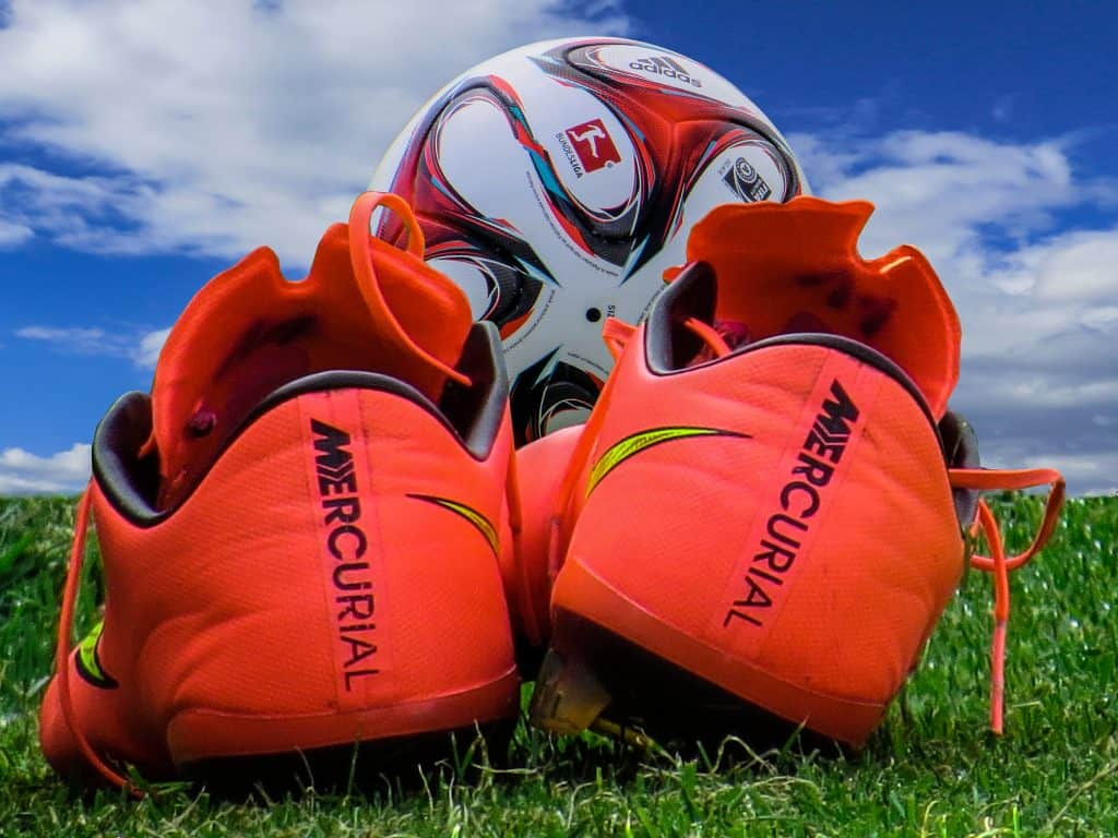 Orange soccer cleats on an outdoor field