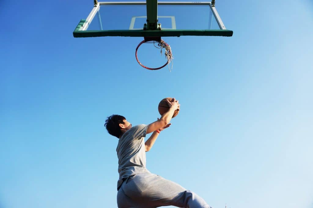 Man jumping to toss a ball into the basketball hoop