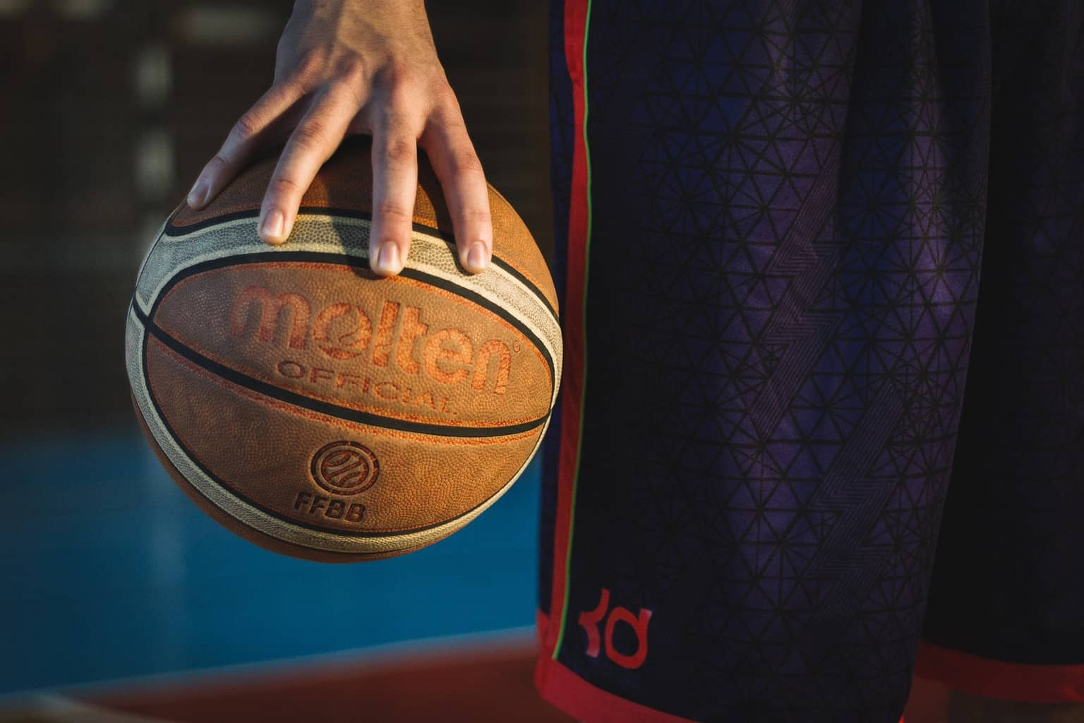 Close up of a person palming a basketball with one hand