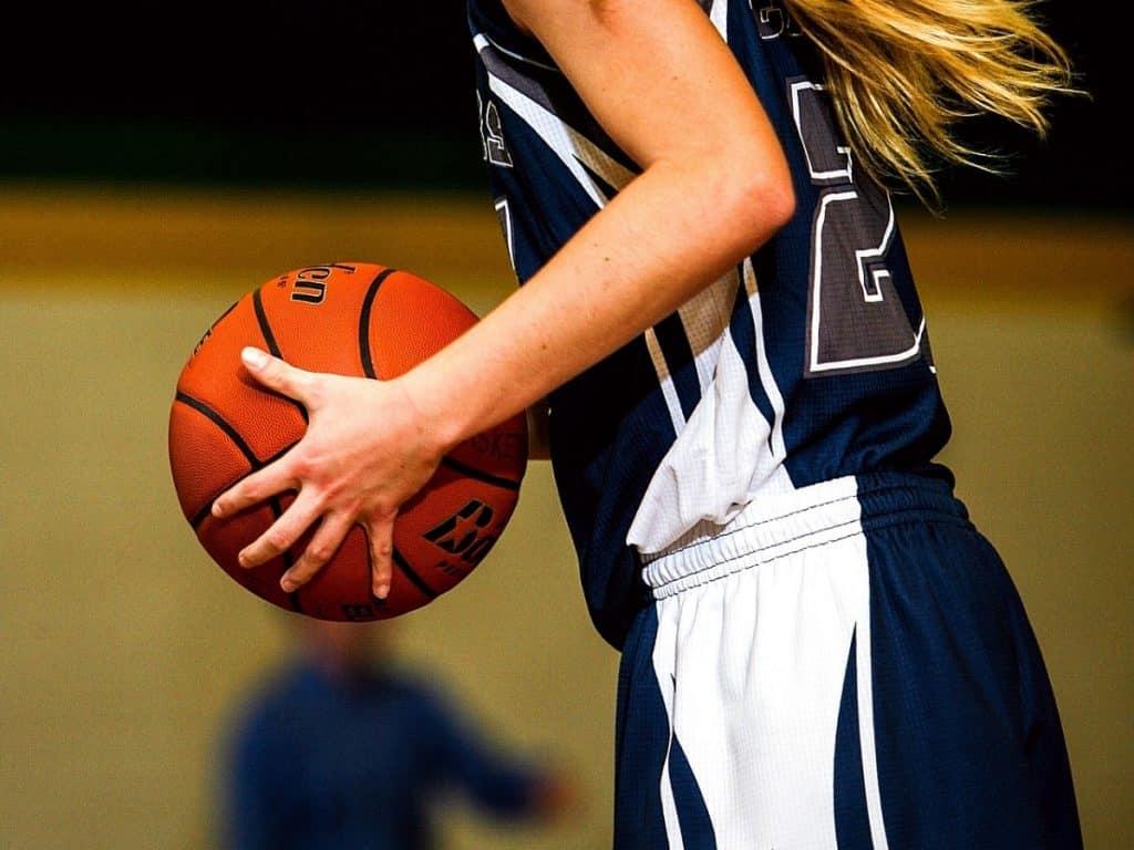 A woman basketball player gripping a ball