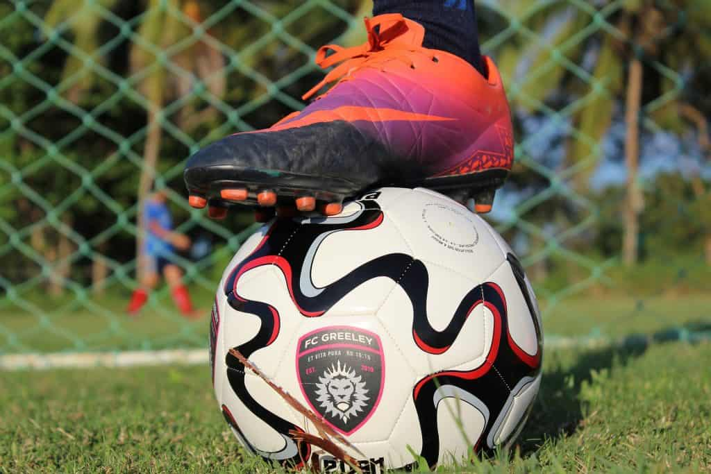 Soccer cleats over a soccer ball