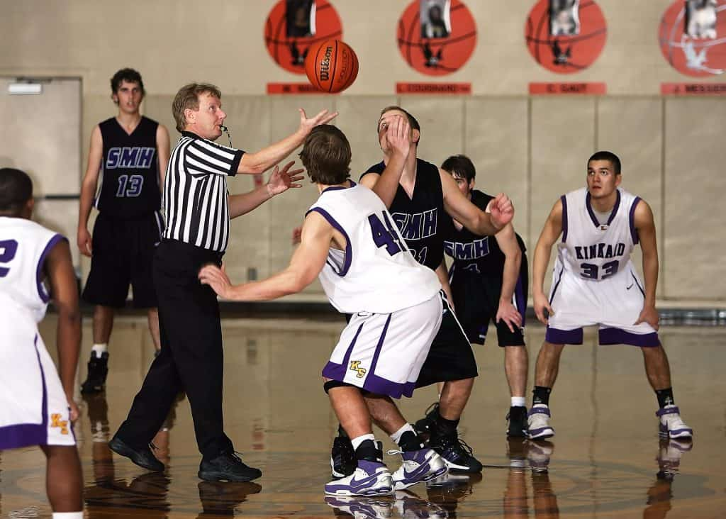 A basketball referee commencing the game with a jump ball