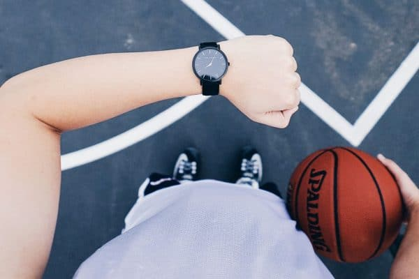 Point of view shot of a boy holding a basketball and looking at his watch