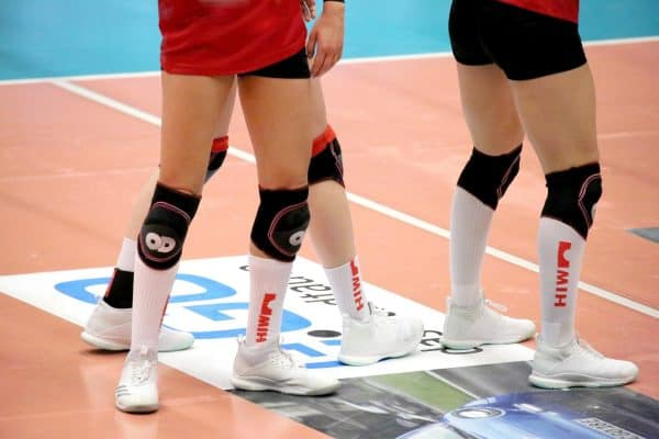 Close up of volleyball players wearing their knee pads, long socks and white shoes
