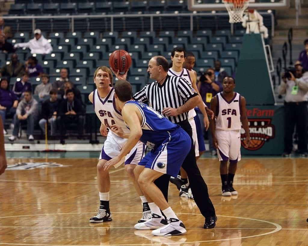 A referee calls the game with a jumpball
