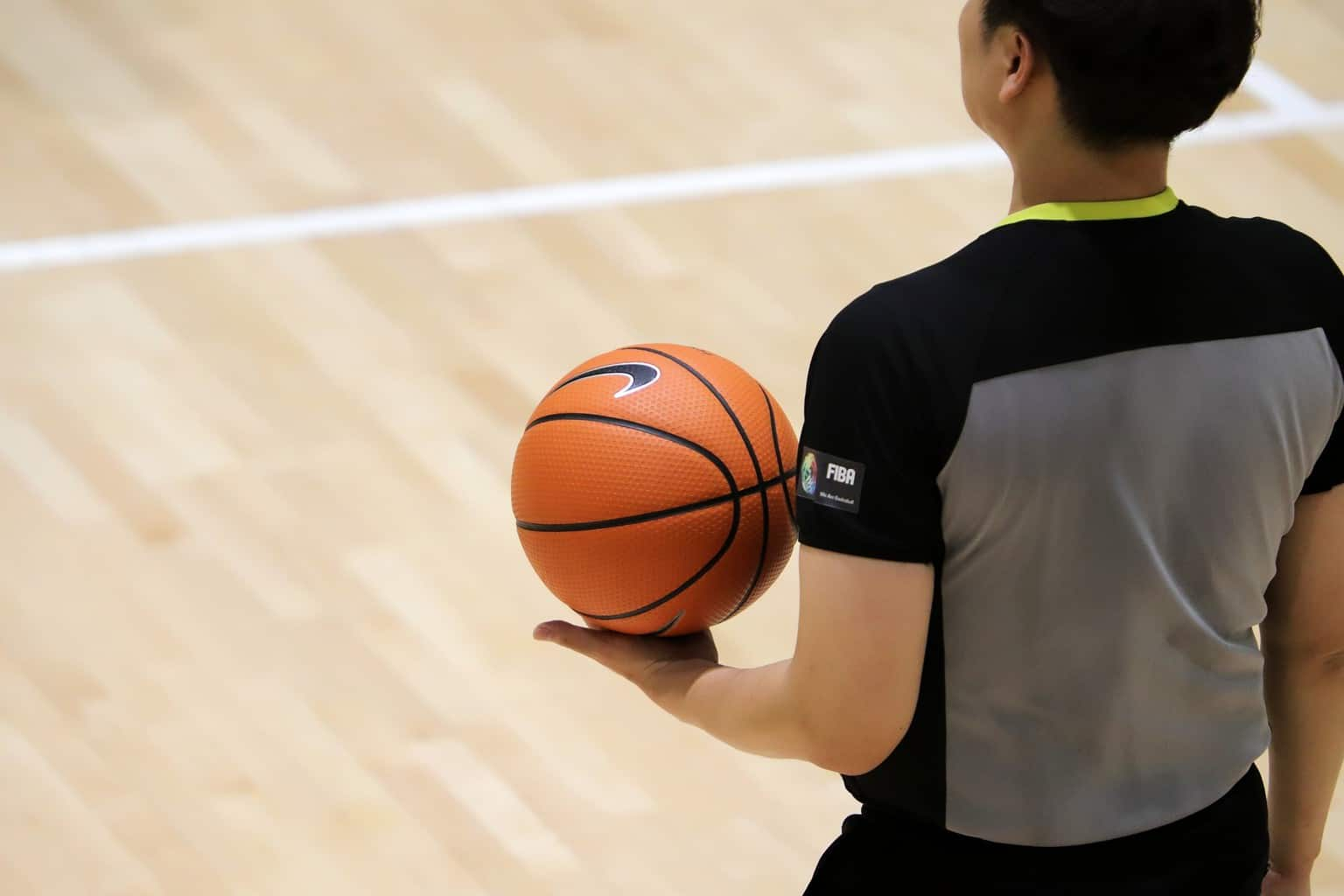 A basketball referee holding a basketball in the court