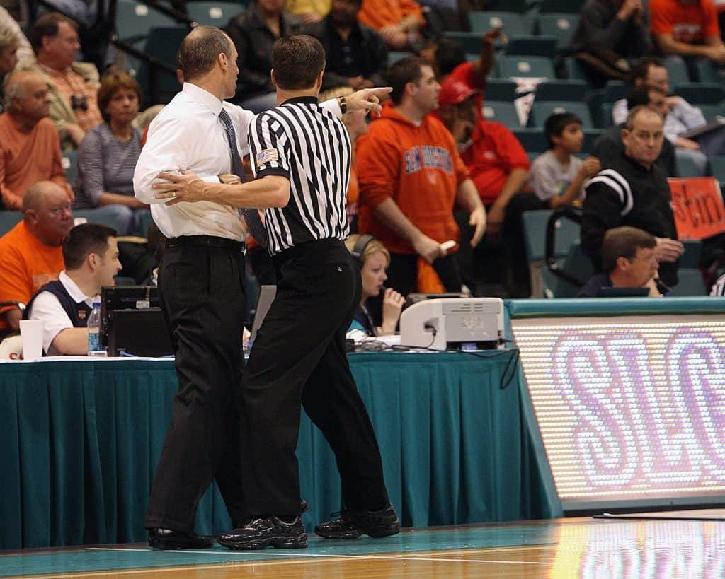 A basketball referee holding back a team coach