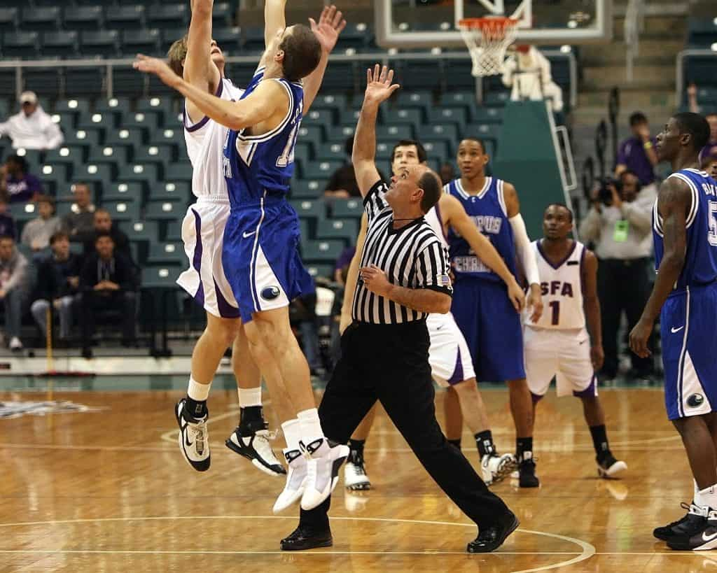 A referee commencing a basketball game with jump ball