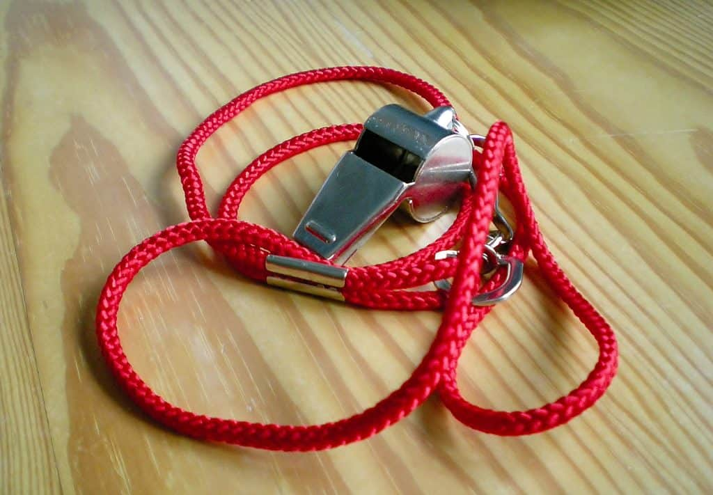 A whistle with a red lanyard on a basketball court floor