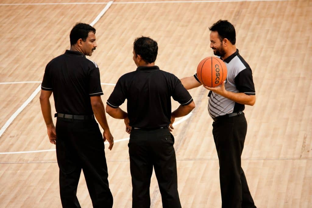 Basketball referees chatting before the game