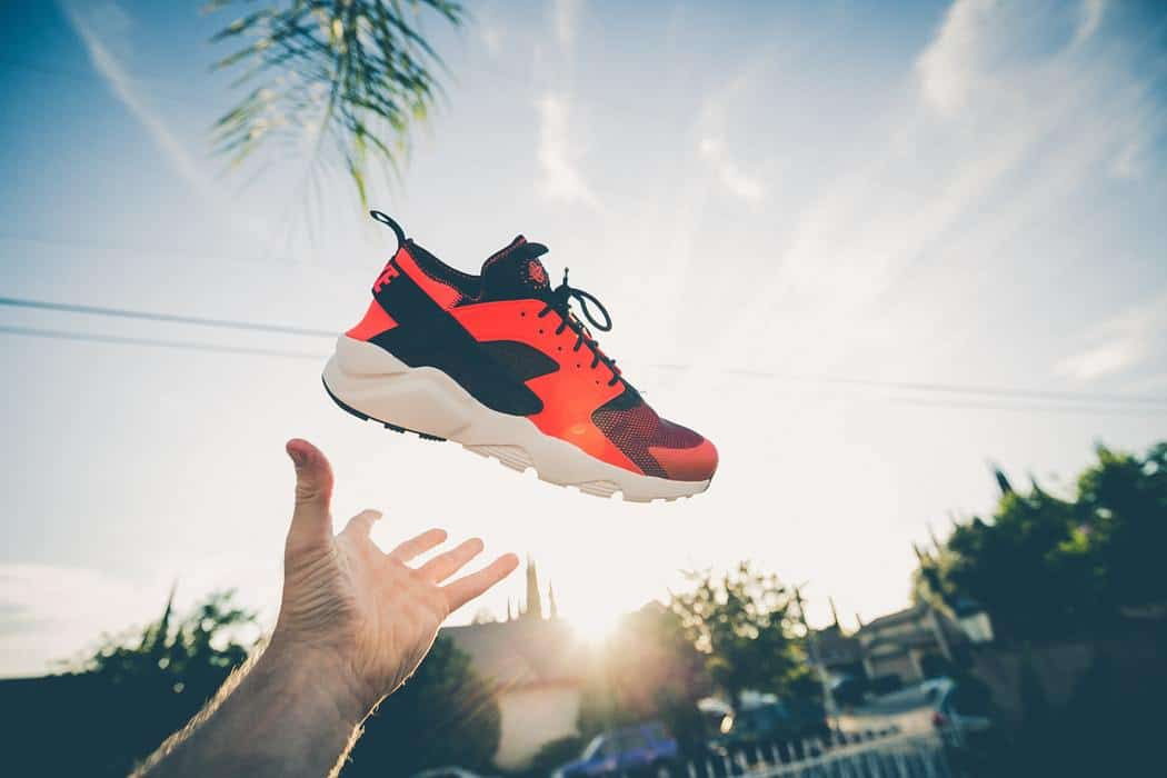A hand throws a red and black basketball shoe in mid air