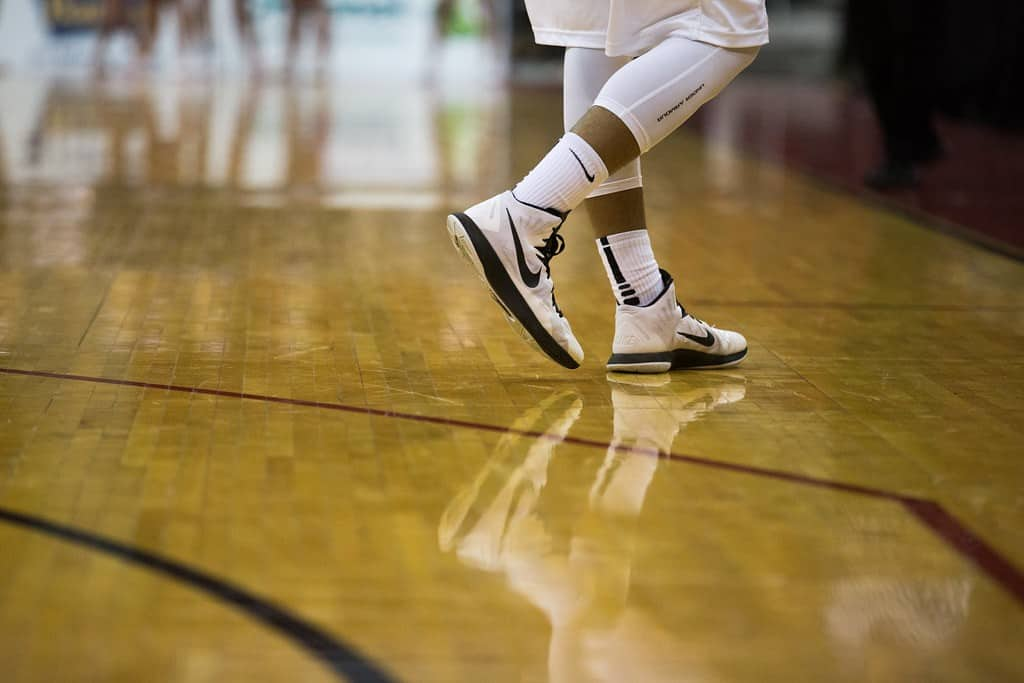 Close up of a person wearing white basketball shoes and long socks