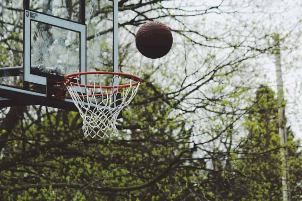 A basketball about to enter through the hoop