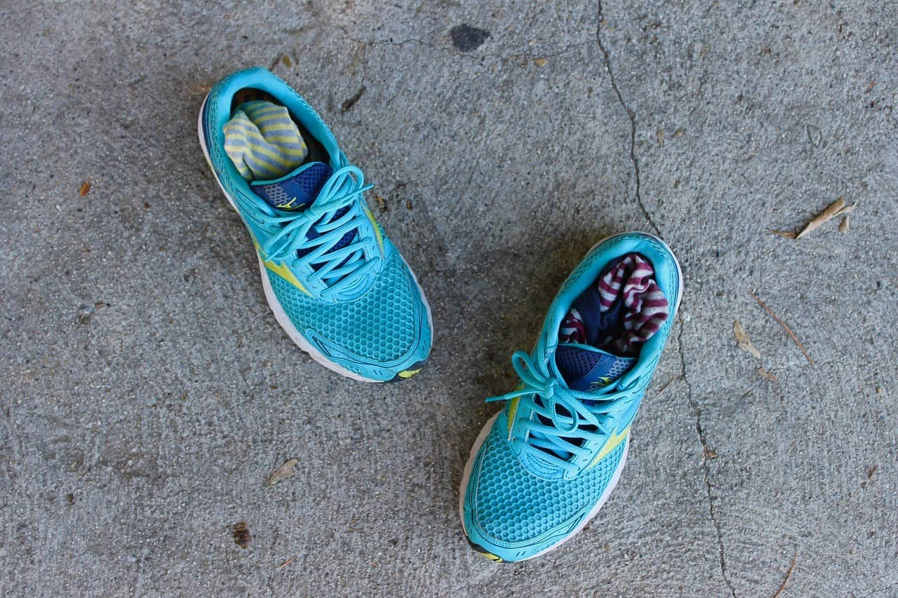 A pair of blue basketball shoes lying on a cement ground