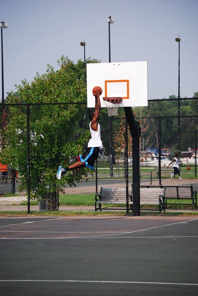 Man doing a jump net shot in a basketball court outside while wearing basketball shoes
