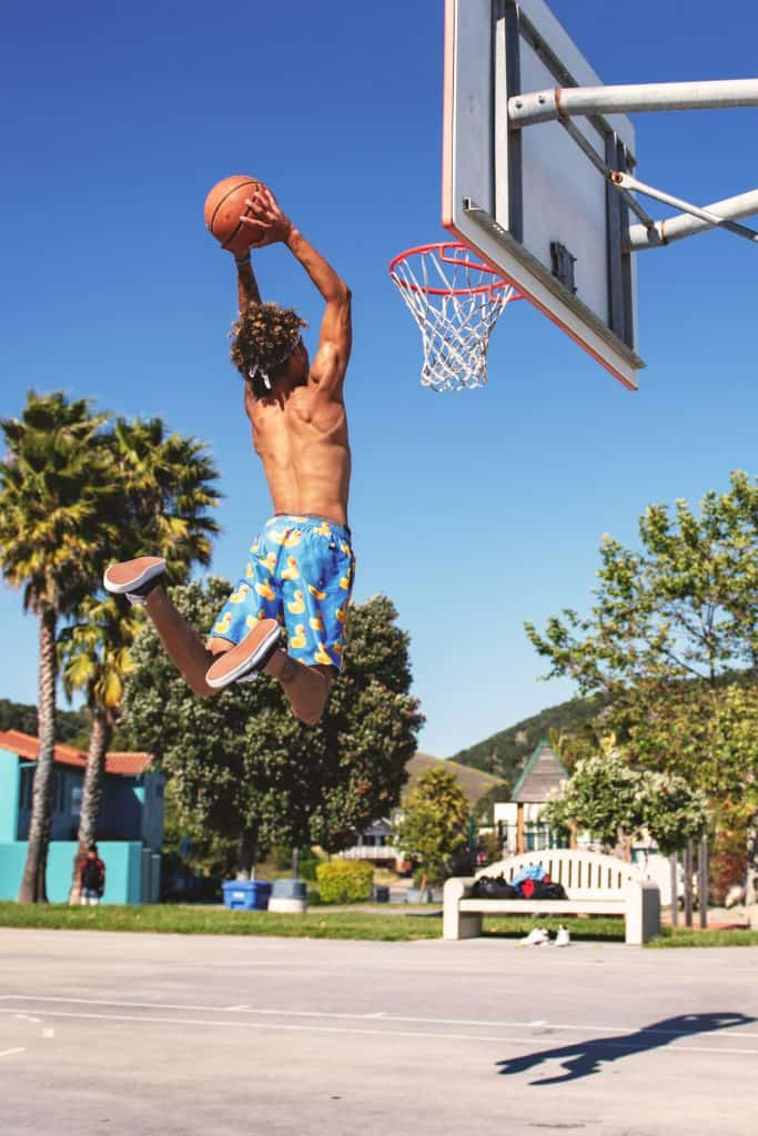 Man attempting to do a jump net shot in an outside basketball court