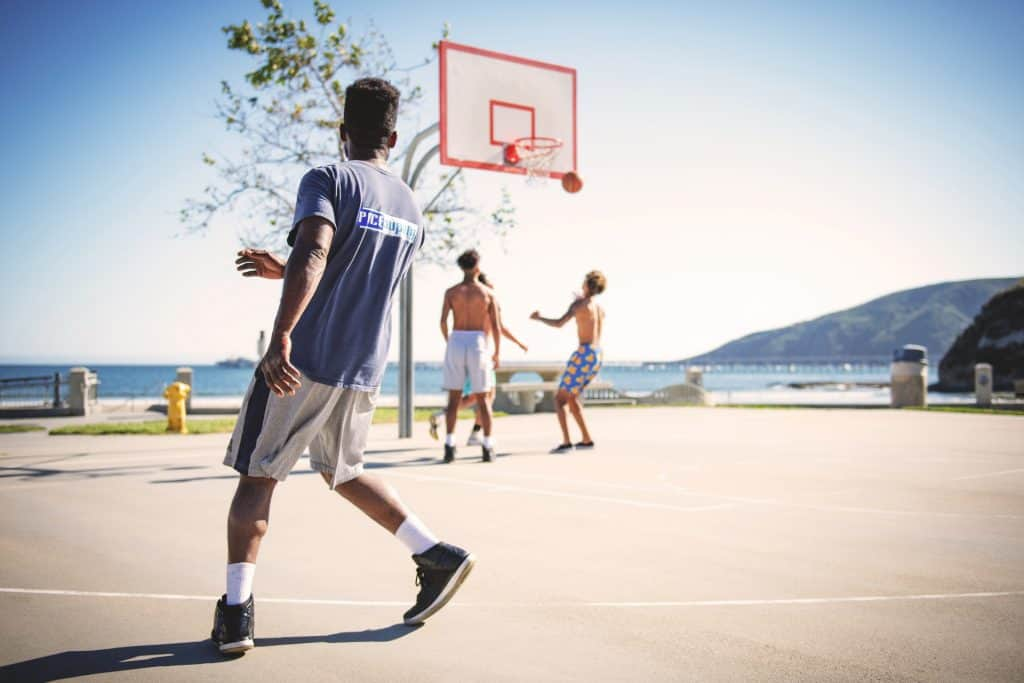 Men playing a game of basketball in an outside court