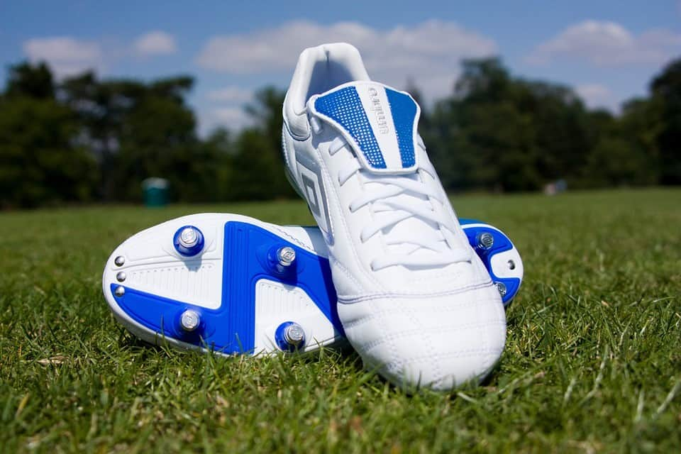 White and blue soccer cleats laying on the grass