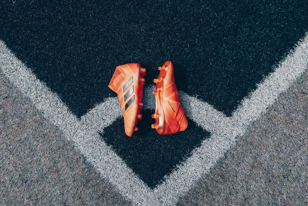 A pair of orange soccer cleats