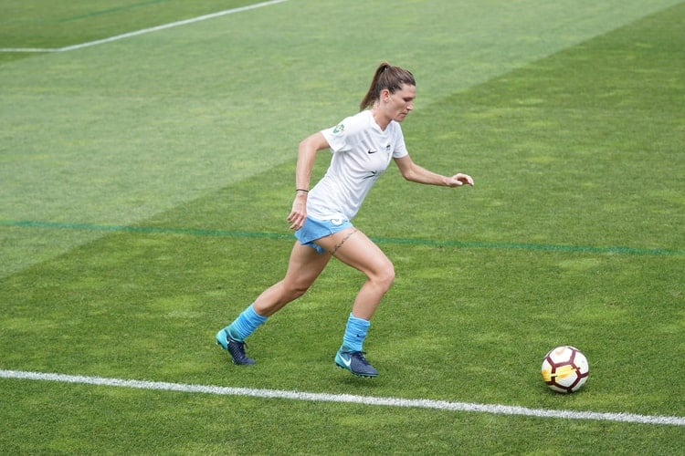 Woman playing in the field while wearing soccer cleats