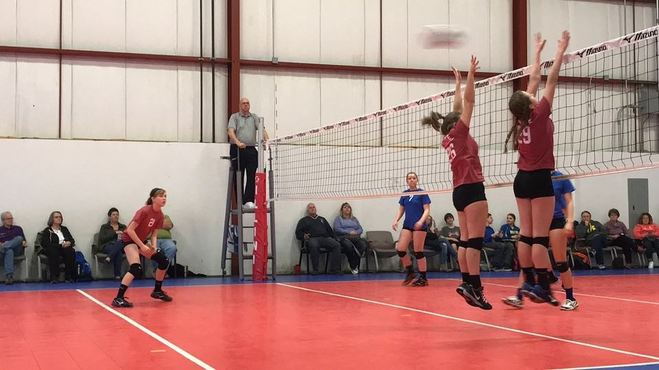 Volleyball players during a game wearing black shoes, red shirts and black shorts