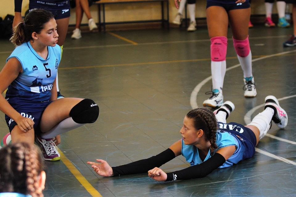 Women in blue volleyball attire resting in the court