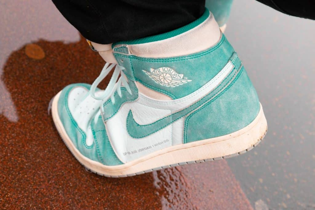 Person wearing white and teal colored basketball shoes stepping on wet surface
