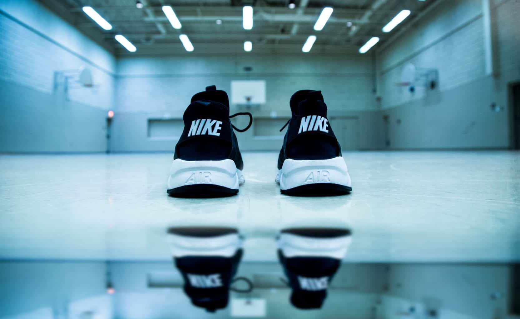 A pair of black Nike shoes placed on an empty gym floor