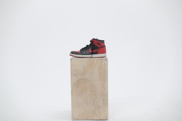 Red and black Nike basketball shoe placed on top of a wood stand
