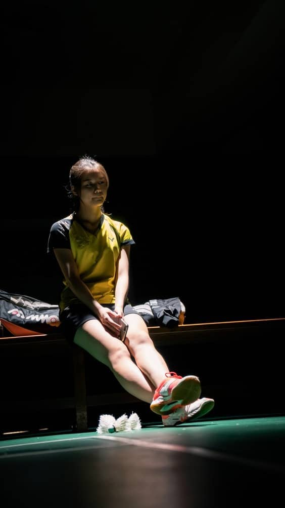 Girl wearing badminton shoes sitting on a bench