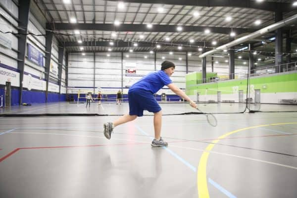 Man playing badminton in an indoor gym while wearing badminton shoes