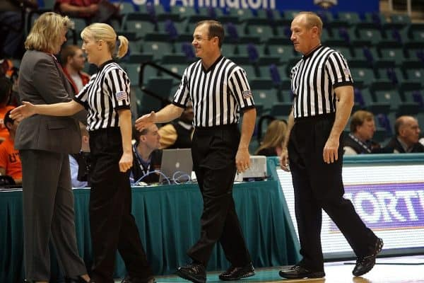 Three basketball referees wearing their uniform and black shoes while lining up to shake hands