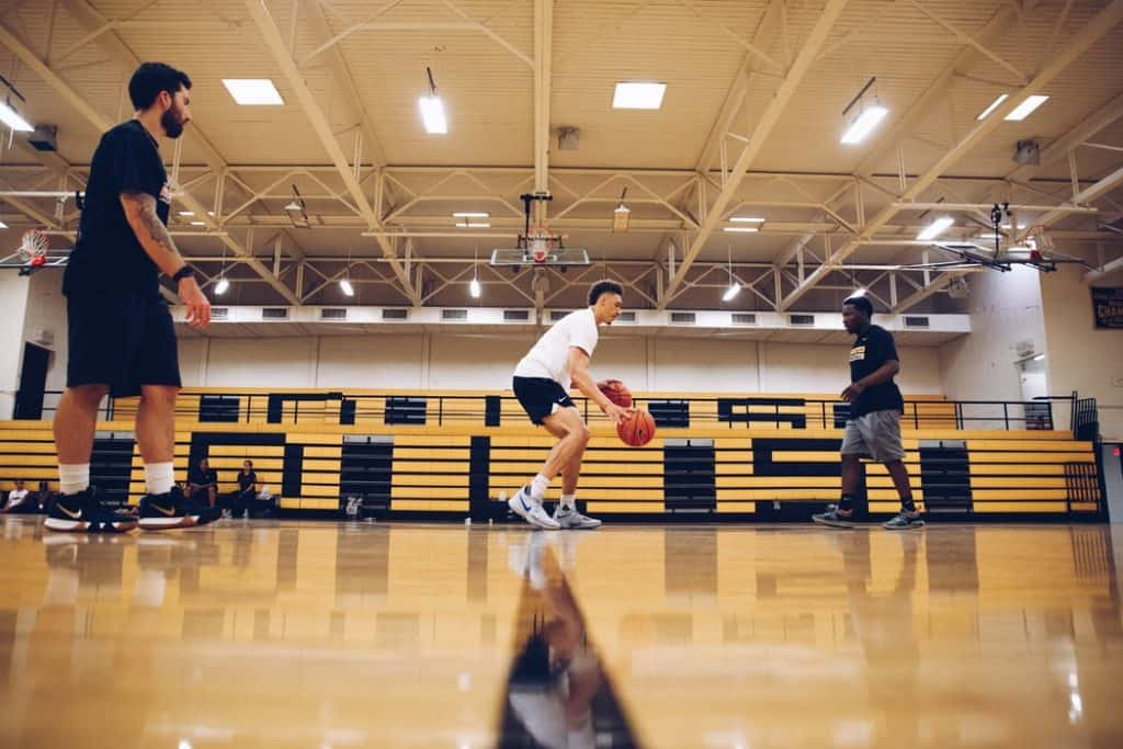 Three men playing basketball in an indoor court
